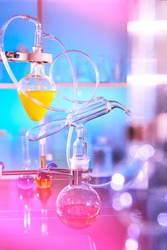 Reaction in progress in organic chemistry lab, distillation glassware, laboratory glass equipment. Futuristic neon lights, bold vibrant purple, pink, blue and turqiouse lights. Experiment in progress.