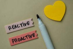 Reactive and Proactive write on sticky notes isolated on office desk.