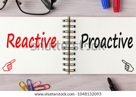 Reactive or Proactive written on notebook on wooden desk with marker pen and glasses.Business Concept.Top view.