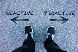 Reactive vs Proactive text on asphalt ground