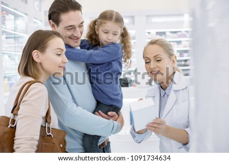 Read attentively. Adorable family listening to female pharmacist and looking down