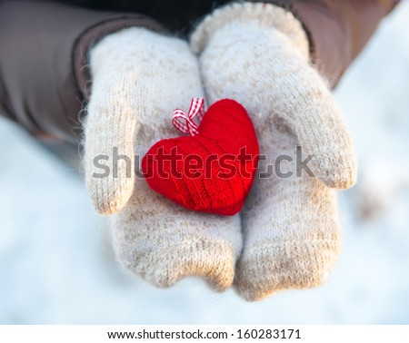 Read heart in white warm wool gloves