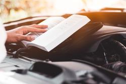 Read the car maintenance manual,Engine maintenance, car care concept.