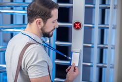 Reader device. Dark-haired young bearded man in profile applying his badge to reader on turnstile