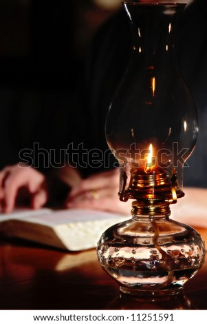 Reading a Bible by vintage oil lamplight - (shallow focus point on antique oil lamp).