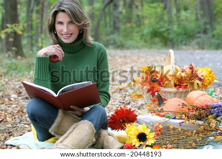 Reading a book in a park - attractive female having a leisurely day in a park, reading a book, in a fall setting with flowers and baskets. Suitable for a variety of seasonal, recreational themes