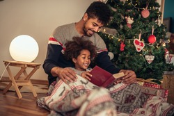 Reading a book to his daughter while lying next to Christmas tree.