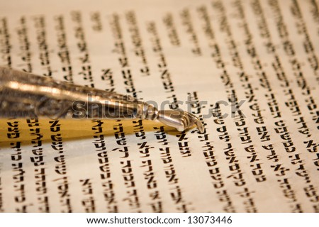 Reading a Torah scroll during a bar mitzvah ceremony with a traditional yad pointing towards the text on the parchment. - stock photo