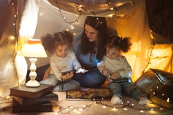 Reading and family games in children's tent. Mother and two twins daughters with books and flashlight before going to bed.