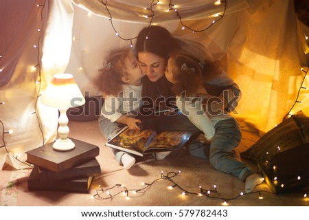 Shutterstock puzzlepix reading and family games in childrens tent mother and two twins daughters with books and flashlight before going to bed sciox Gallery