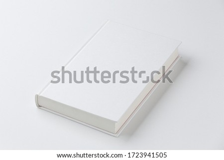 Reading book with a white cover, perched on a white surface. Isolated. Сток-фото ©