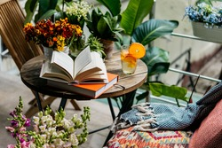 Reading books in summer at a beautiful terrace or cozy balcony full of green plants.