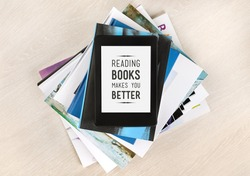 Reading books makes you better - text on a screen of electronic book on top of a pile of books and magazines. Concept of learning new knowledge, self improvement and development of mental abilities