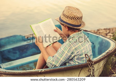Reading boy in old boat #280563209