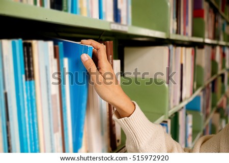 Reading concept. Vintage tone of asian woman selecting book from a bookshelf in library (selective focus).