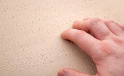 Reading for the visually impaired, school for the blind and vision disability concept with hand touching the pages of a book written in braille with copy space