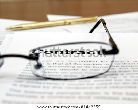 """Reading glasses on papers and word """"contract""""in focus"""