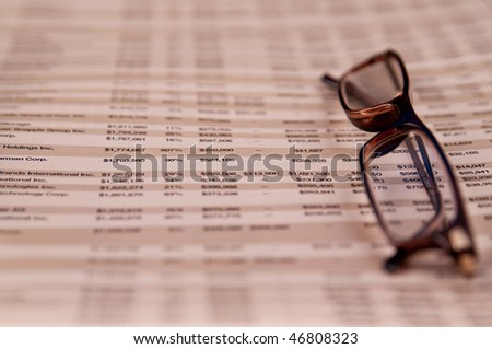 Reading glasses on top of Business page of a financial newspaper
