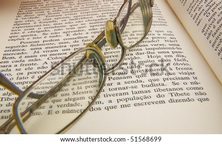 reading glasses on top of old book