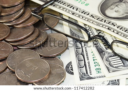 Reading glasses over money Concept about saving money for retirement or rich people having money