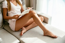 Reading interesting book. Woman in home clothing sitting on sofa and reading book at home.