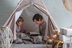 Reading nook. Two cute brothers reading a bedtime story in play room. Cozy room for kids in scandinavian style