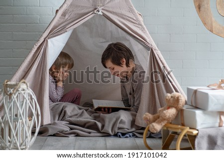 Reading nook. Two cute brothers reading a bedtime story in play room. Cozy room for kids in scandinavian style Foto stock ©