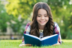 Reading only enhances your knowledge. Happy child read book lying on green grass. School library. Imagination and fantasy. Literacy education. Reading is good hobby.