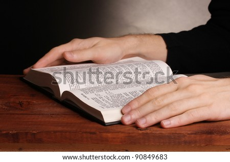 Reading open russian holy bible on wooden table - stock photo