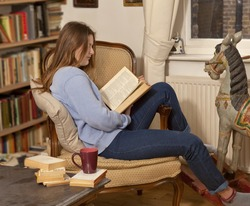 Reading. Reading at home with a cup of tea, a young girl ,draped over her reading chair, absent mindedly plays with her toy of the past with her foot as she reads her heavy book .