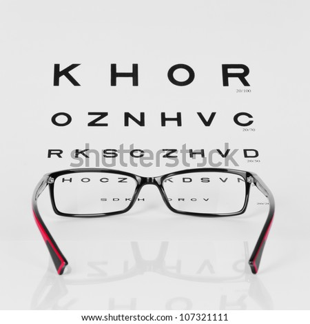 Reading Red and Black eyeglasses and eye chart. close-up. on a light gray background
