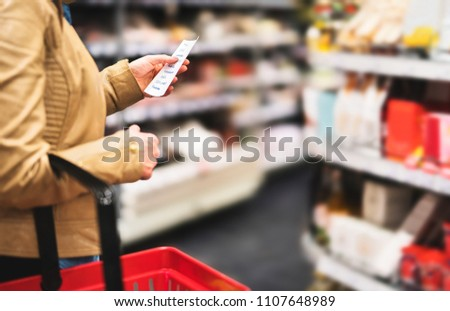 Reading shopping list in supermarket. Female customer in grocery store with budget, plan or checklist. Lady doing groceries and buying food for family. Shopper with basket between shelves in aisle.