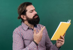 reading the poem. poetic man with beard reading the book. process of studying. nonformal education. male student in school classroom on literature lesson. pass the exam. learning the subject.
