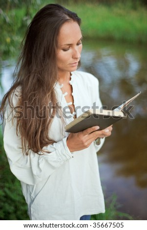 Reading young woman near the river