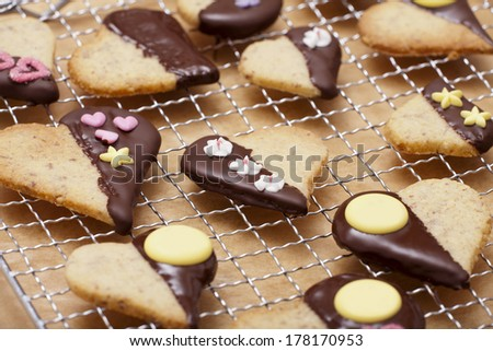 Ready-baked cookies in heart shape with decor sugar on a cake rack #178170953