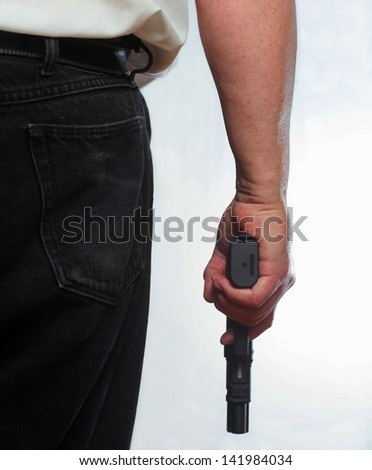 Ready for Action/Close partial image of man from behind holding automatic pistol against white background