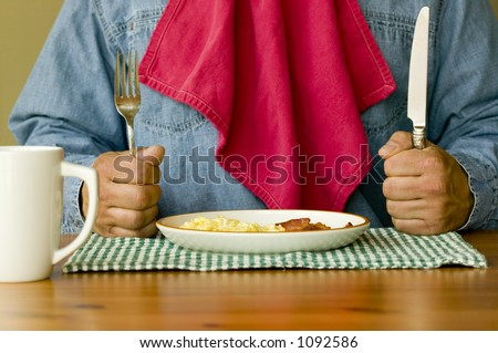 Ready For Breakfast Hungry man holding knife and fork with napkin tucked in shirt ready to eat bacon and eggs for breakfast.