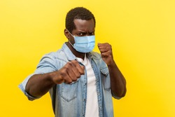 Ready for fight against coronavirus. Portrait of aggressive man with surgical medical mask standing in defensive posture, clenched fists, threatening to attack. indoor, isolated on yellow background.