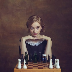 Ready for game. Young woman in art action isolated on brown background. Retro style, comparison of eras concept. Beautiful female model like legendary chess player, queen or duchess, old-fashioned.