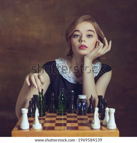 Ready for game. Young woman in art action isolated on brown background. Retro style, comparison of eras concept. Beautiful female model like legendary chess player, queen or duchess, old-fashioned. Zdjęcia stock ©