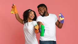 Ready For Spring-Cleaning. Portrait of joyful african couple with household supplies in hands over pink background