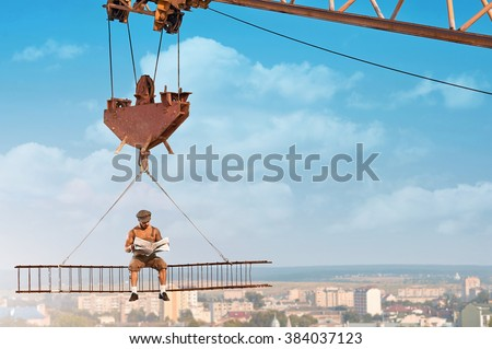 Ready for the news. Fearless old fashioned builder man reading a newspaper sitting on a crossbar hanging on a crane above the city
