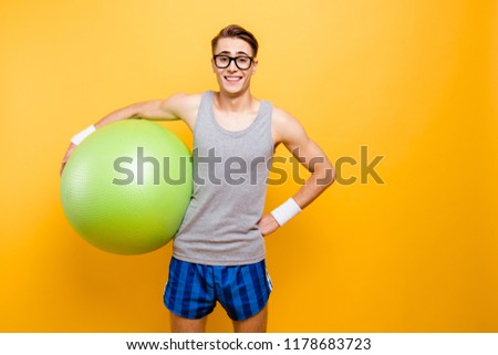 Ready for training! Portrait of careless, carefree man holds a big green ball at hand, make good beaming smile isolated on shine yellow background with copy space for text
