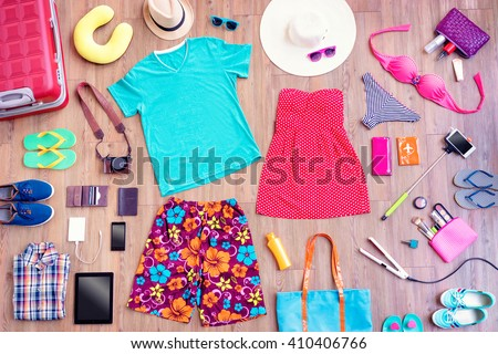 Ready for travel. Overhead of essentials for vacation. Top view of male and female summer accessories, clothes and gadgets on the wooden background. Packing suitcase.