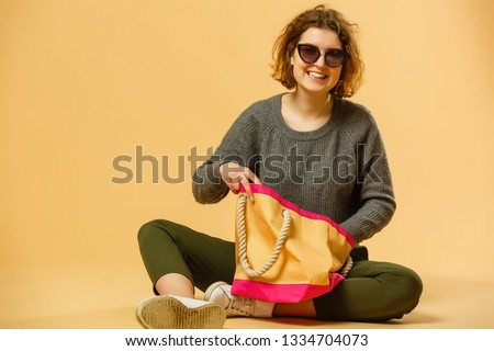 Ready for vacation. Traveling concept. Young excited woman sitting luggage valise. Isolated