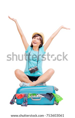 Ready for vacation. Traveling concept. Young excited woman sitting on the luggage valise. Isolated on white.