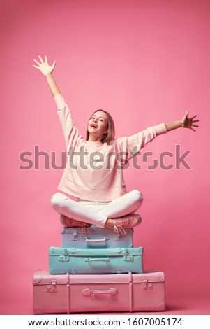 Ready for vacation. Traveling concept. Young excited woman sitting on the luggage valises. Pink background.
