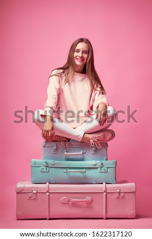 Ready for vacation. Traveling concept. Young happy woman sitting on the luggage valises. Pink background.