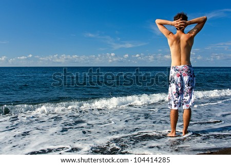 Ready for vocation. Young and healthy man wearing swimming trunks standing on the beach and looking at the sea.