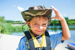 Ready kayaking. Portrait of happy little boy near the river and enjoying a lovely summer day